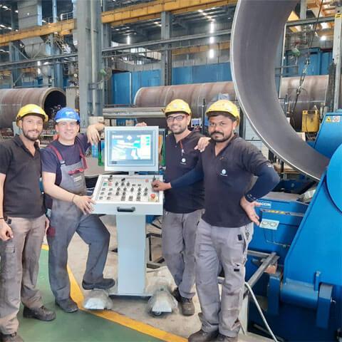 Faccin: cilindradora para la construcción de torres eólicas controlada con CNC Siemens con una lámina metálica curvada; 2 técnicos y 2 operadores